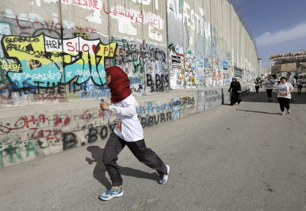 Participants run past Israeli barrier during Palestine Marathon in the West Bank town of Bethlehem