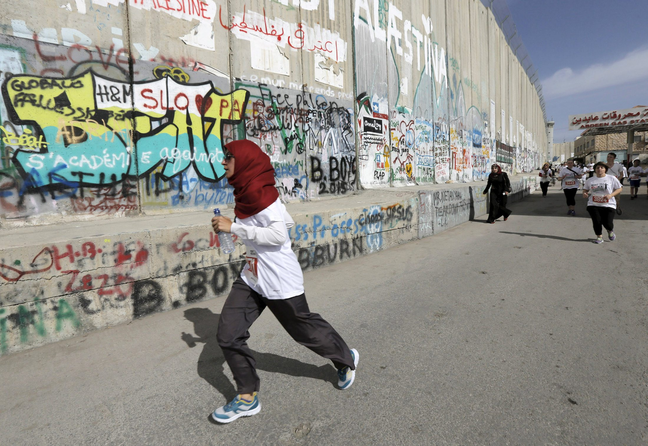 Participants run past Israeli barrier during Palestine Marathon in the West  Bank town of Bethlehem 8c6afa46faa6b
