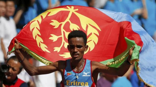 REFILE - CORRECTING BYLINEGhirmay Ghebreslassie of Eritrea celebrates with his country's flag after winning  the men's marathon at the 15th IAAF World Championships at the National Stadium in Beijing, China August 22, 2015.  REUTERS/Lucy Nicholson